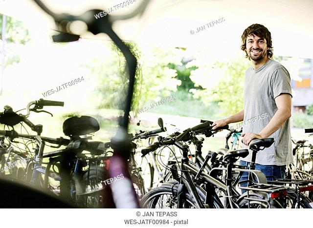 Portrait of smiling young man parking his bicycle