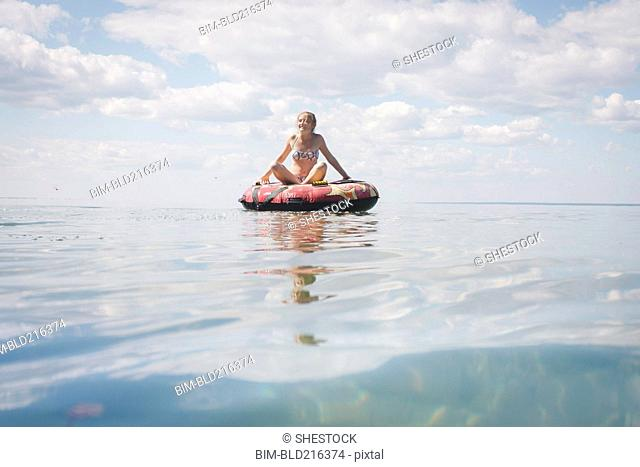 Caucasian teenage girl floating in inner tube on lake