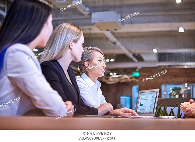 Colleagues in open plan office in business meeting