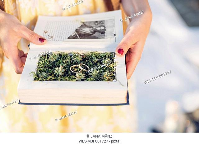 Woman's hands holding prepared book with two wedding rings lying on moss