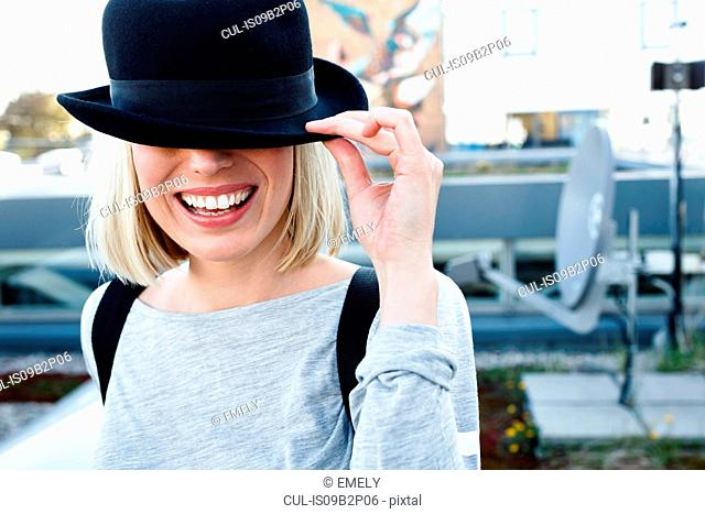 Portrait of blonde haired woman wearing hat over eyes smiling