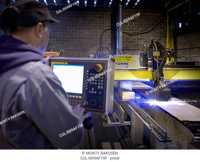 Engineer using plasma cutter in factory