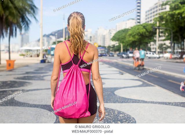 Brazil, Rio de Janeiro, back view of woman walking on pavement
