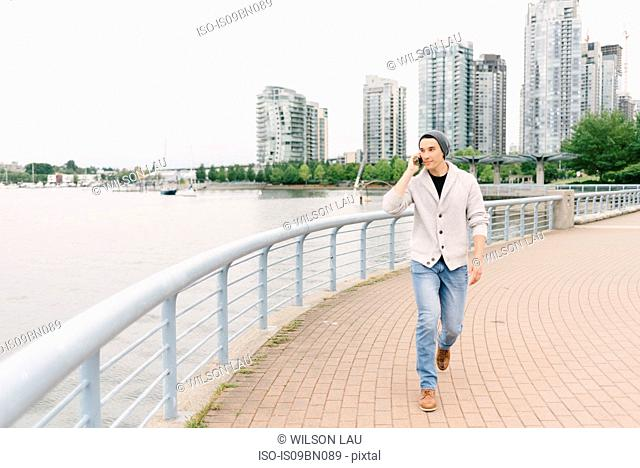 Young man talking on phone while walking along seawall, Yaletown, Vancouver, Canada
