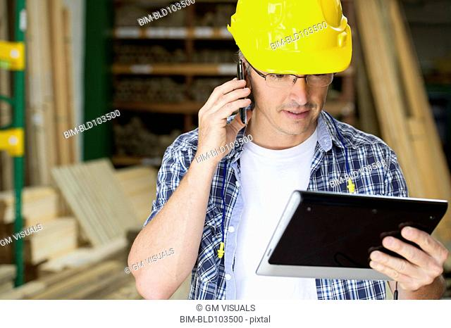 Hispanic carpenter using cell phone and digital tablet