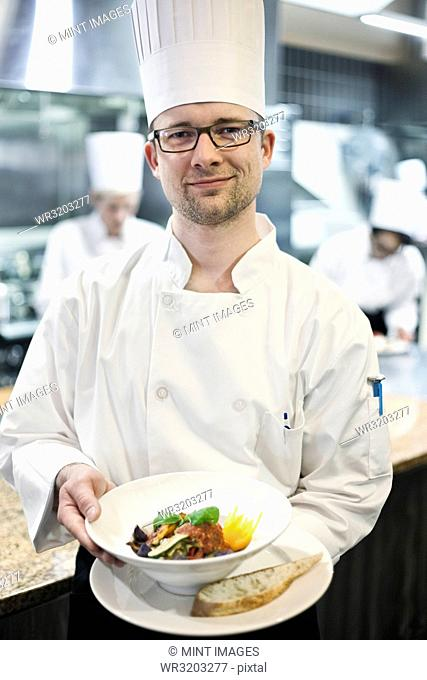 A Caucasian male chef presenting a finished plate of fish in a commercial kitchen