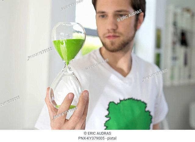 Man looking at an hourglass with green sand in it