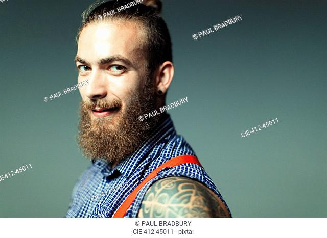 Portrait confident, cool male hipster with beard and shoulder tattoo