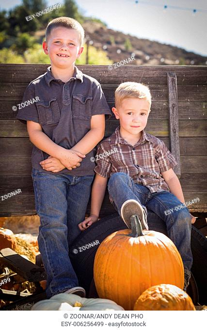 Two Boys at the Pumpkin Patch Against Antique Wood Wagon