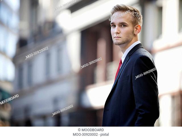 Portrait of handsome businessman in suit standing against building
