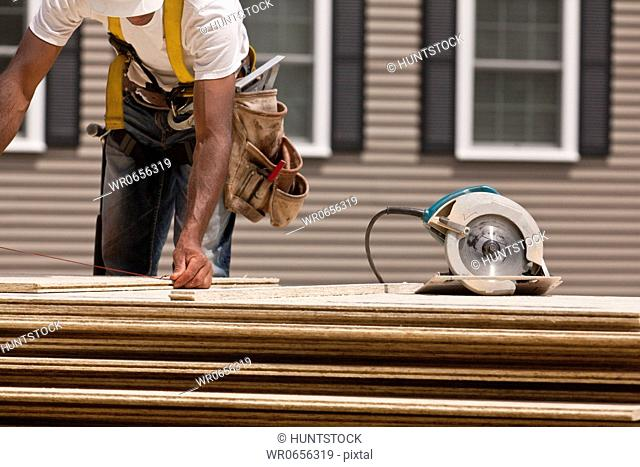 Carpenter using a snap line before sawing