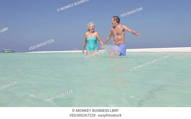 Senior couple running through sea towards and past camera.Shot on Canon 5d Mk2 with a frame rate of 30fps