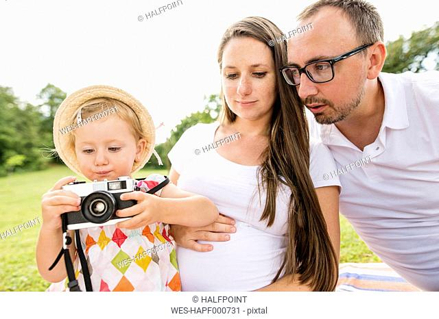Happy family in park, daughter playing with camera