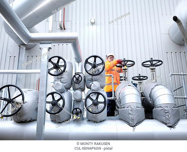 Worker turning valve of gas fired power station