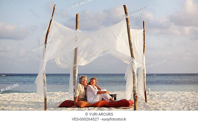 Loving couple sitting on a beach together enjoying the sunset and a light breeze