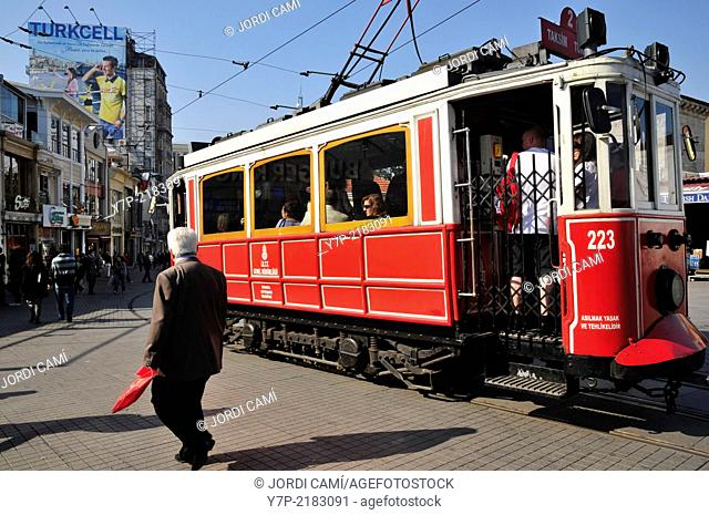The old tram in the confluence of Istiklal Cadessi and Taksim Square and Turkcell cellular phone operator publicity placard . Istanbul. Turkey