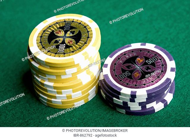 Poker chips, yellow and purple, stacked on green felt