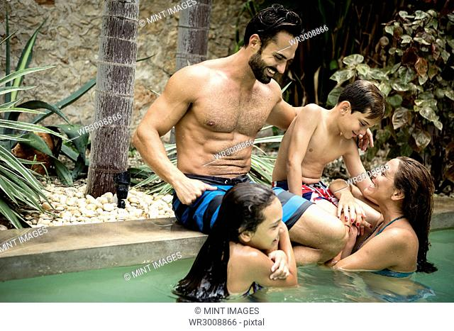A family hugging in a swimming pool