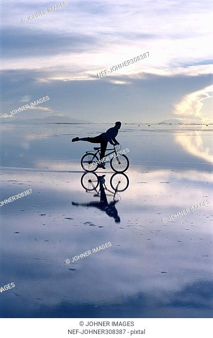 Silhouette of person cycling in the desert