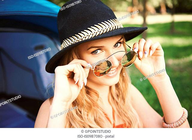 Portrait of young boho woman holding sunglasses at festival