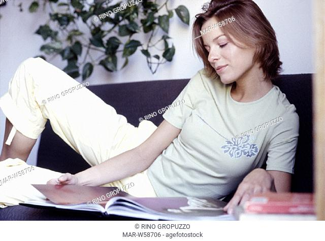 woman sitting on sofa reading magazines
