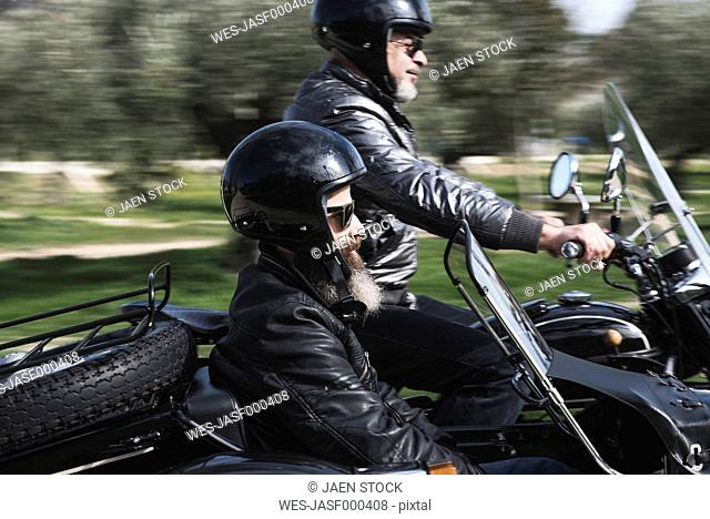 Two bikers driving with their sidecar motorcycle