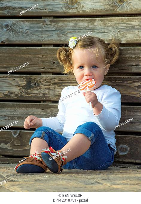 Young girl with blond hair and blue eyes sitting and eating a lollipop; Tarifa, Cadiz, Andalusia, Spain