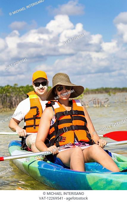 Couple in double kayakers floating in magrove lagoon with blue sky and clouds; Tulum, Quintana Roo, Mexico