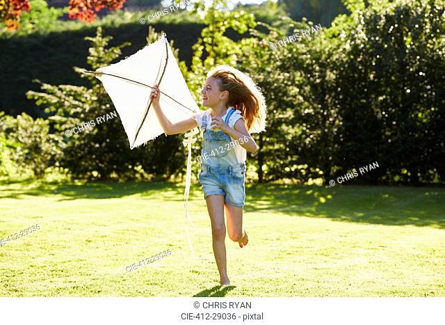 Girl running with kite in sunny garden