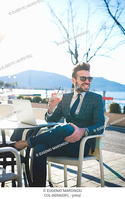 Businessman with laptop having a drink at lakeside cafe, Rovato, Brescia, Italy