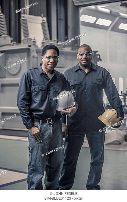 African American workers standing together in factory