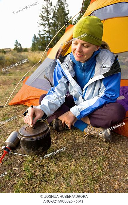 A young woman making coffee during a camping trip in Grand Teton National Park, Wyoming