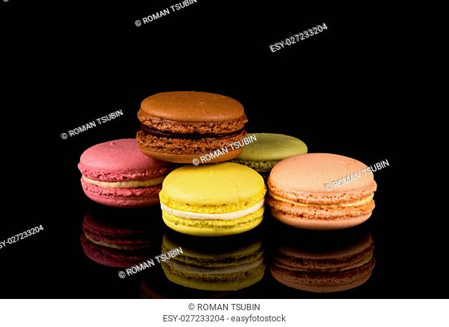 Colorful pink macaroon over a black background