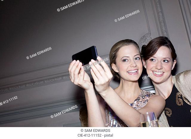 Smiling women taking self-portrait with camera phone