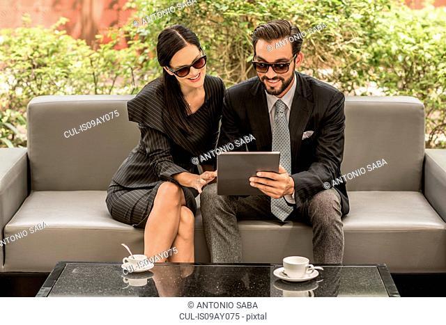 Businessman and woman reading digital tablet on hotel garden sofa, Dubai, United Arab Emirates