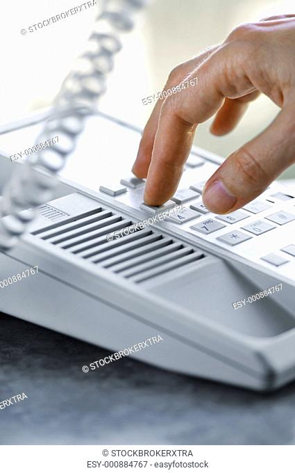Close up of fingers dialling a desktop telephone