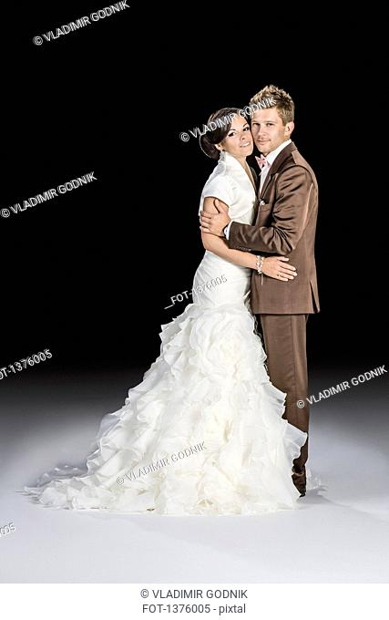 Full length side view of bride and groom standing against black background