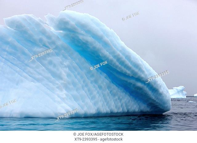 iceberg showing straight striped lines and water line erosion near cuverville island Antarctica