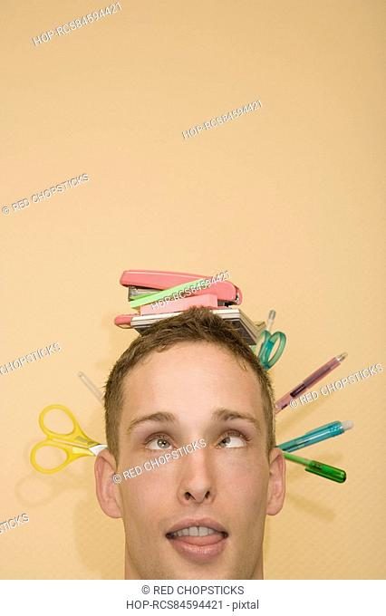 Close-up of a young man with stationery objects on his head