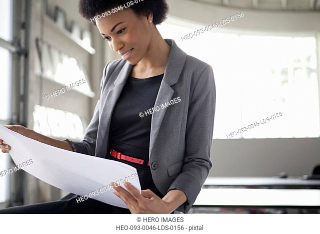 stylish businesswoman reviewing plans in office