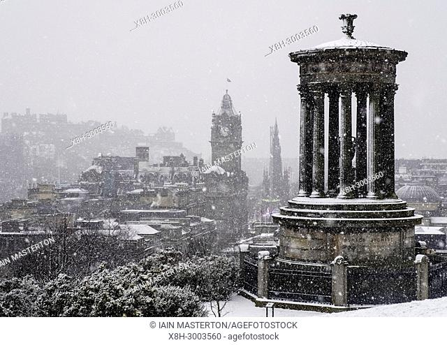 Snow falls on city of Edinburgh in December. Skyline view of city from Calton Hill, Scotland, UK