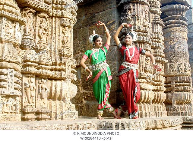 Dancers performing classical traditional odissi dance at Konarak Sun temple , Konarak , Orissa , India MR 736D,736C