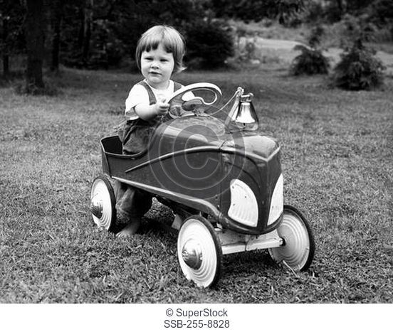 Portrait of girl driving toy car