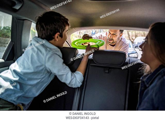 Fathe giving boy flying disc in car