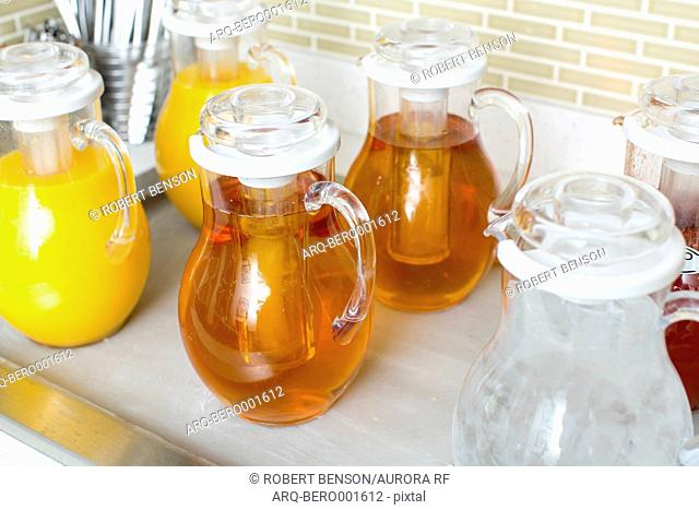 Jars fill with fruit juice stow on a kitchen counter