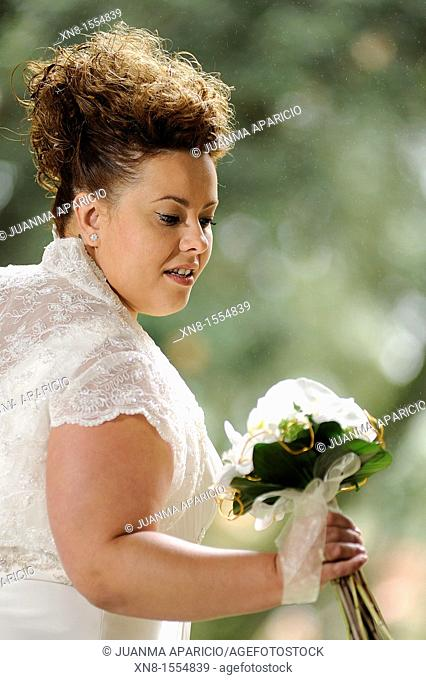 Attractive young woman in wedding dress, looking at her bouquet