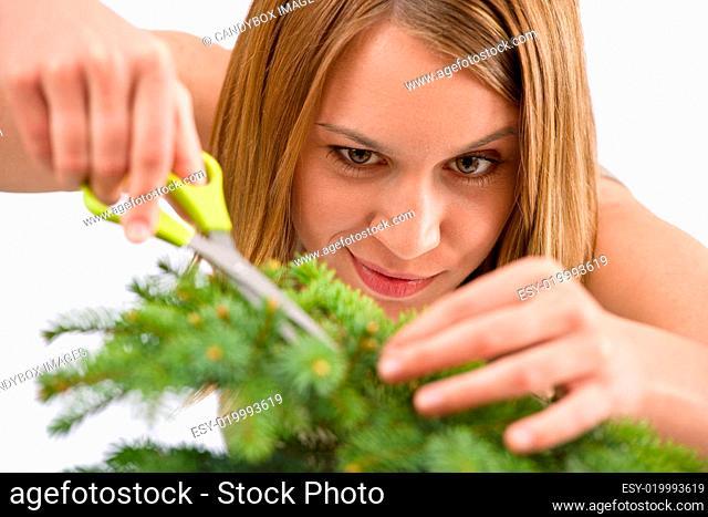 Gardening - woman trimming spruce tree, focus on scissors