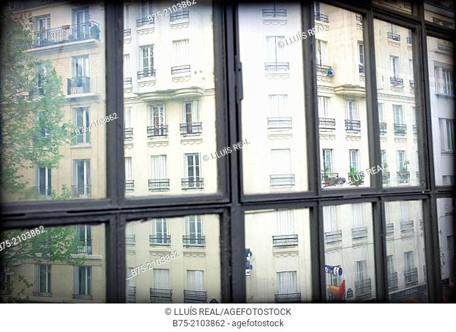 Paris apartment building seen from behind a window, France
