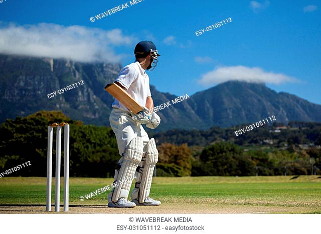 Full length of cricket player practicing against blue sky