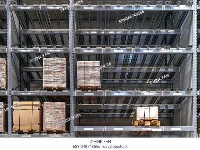The warehouse full of goods, boxes and shelves in order, industrial background